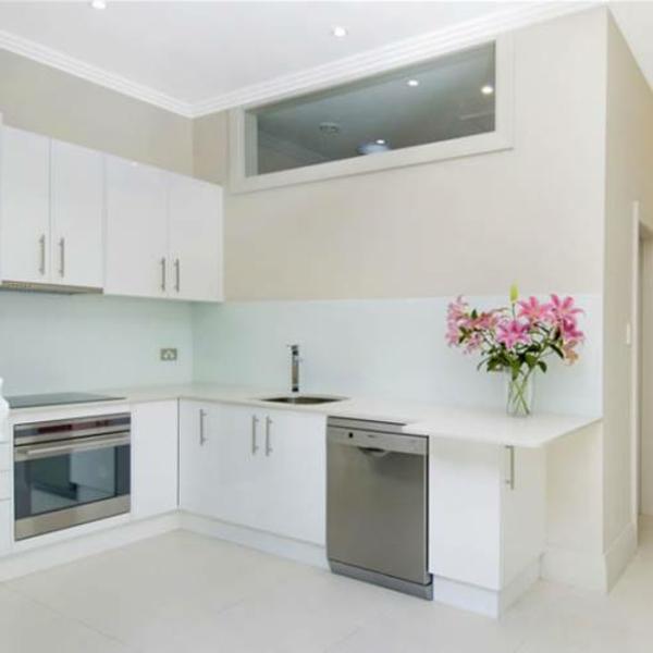 Белая кухня с рисунком на фартуке