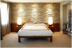 Ощущение теплой пещеры в спальне со стеной из декоративного камня