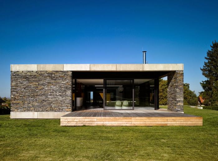 Небольшой дом с плоской крышей и темной фасадной плиткой под камень