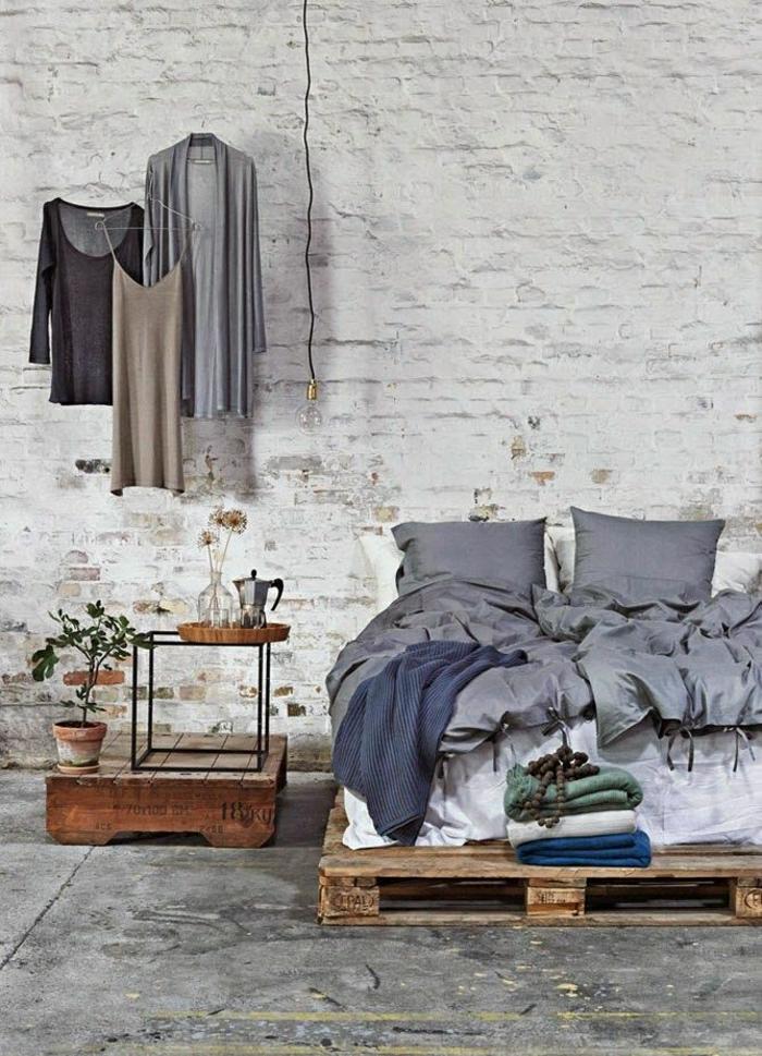 Кровать из поддонов в комнате в индустриальном стиле
