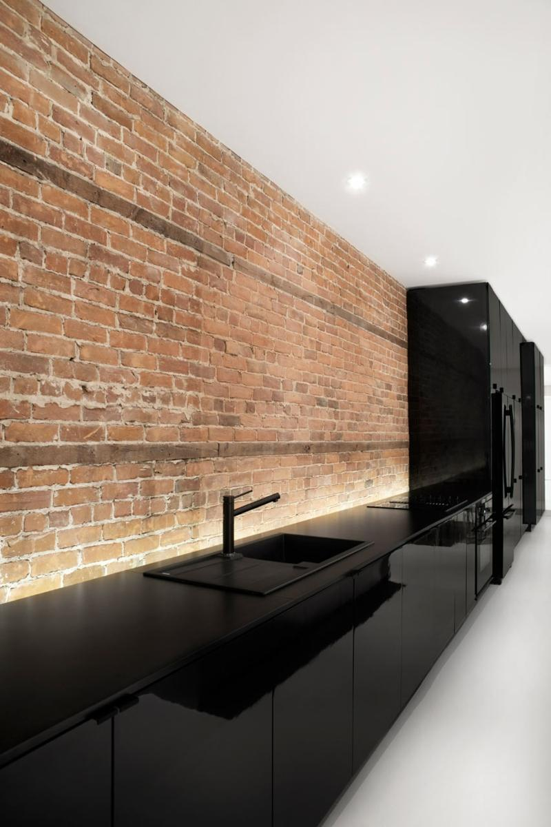 дизайн черной кухни фото интерьер с черной столешницей кирпичной стеной подсветкой