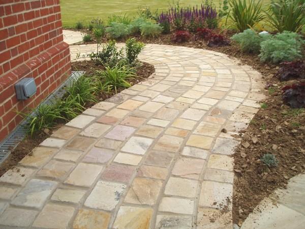 pflastersteine-verlegen-naturstein-material-verwenden-schon-gebogen-gartenweg-haus